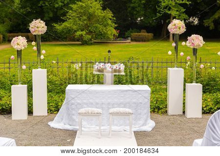 Scenery of the wedding ceremony in the park. White frame decorated with flowers. Ceremony in white style.