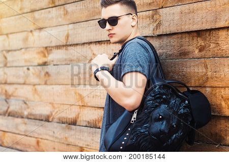 Portrait of young beautiful fashionable man. vintage photo. The guy standing near the old wooden wall. In the hands of a fashion backpack and a lion, sunglasses
