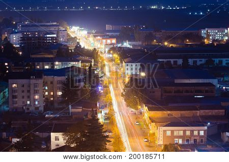 Gori, Shida Kartli Region, Georgia. Cityscape With Night Streets In Bright Yellow Evening Illumination In Twilight. Aerial View Of City. Traffic Trails Lights