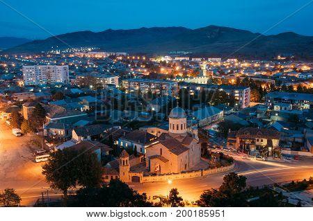 Gori, Shida Kartli Region, Georgia. Gori Cityscape In Evening Illumination Under Blue Sky In Twilight. Cathedral Of The Blessed Virgin Mary In Night Illuminations Lights. Travel Destination