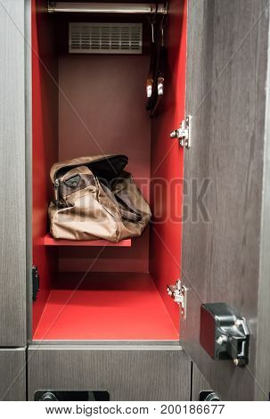 Brown sport bag sitting in men locker room with opened door showing interior red finishing. Free service in fitness.