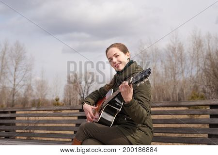 Smiling woman playing the guitar on a wooden bench outdoors