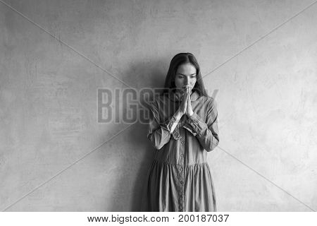Sad woman standing beside the grunge wall. Black and white retouched image.