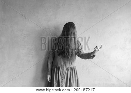 Evil woman beckoning someone with her finger. Her face is covered with hair. Retouched black and white image.