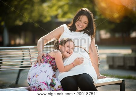 Young smiling happy girl listening to her pregnant mother's tummy
