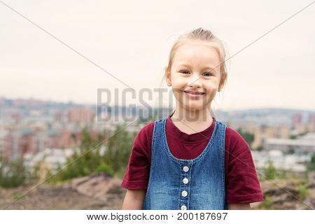Little 4-year-old girl with a nice smile on her face outdoors on a summer day.