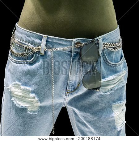 Stylish light blue jeans with chain accessories and sunglasses on waist against black background. Vintage denim with skinny and low-rise pattern for new generation fashion.