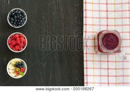 Smoothie with blueberries banana and raspberries in jar with place for copy-space on black wooden background. Selective focus. Healthy food Clean Eating or Vegetarian concept.