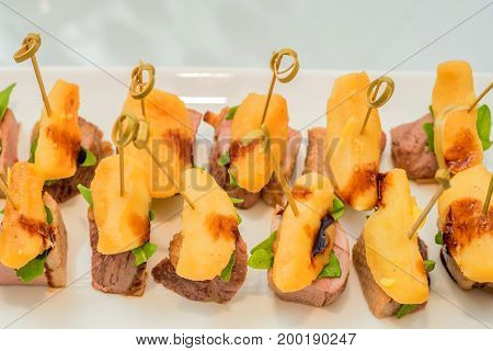 Close up tasty appetizer made of potato wedges and meat on skewers