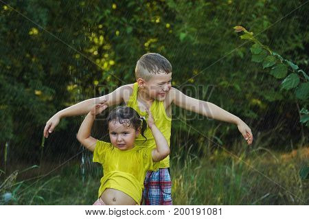 Brother and sister playing in the summer rain