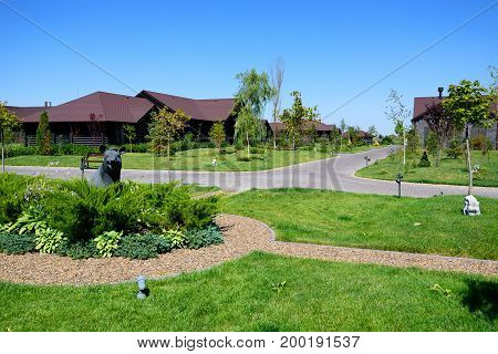 Beautiful picture of summer cottages and green alley with paths on sunny day