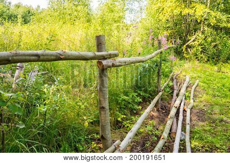 Fence is handmade from trees trunk. The rural design of the fence site. Fence for the cattle in the village.