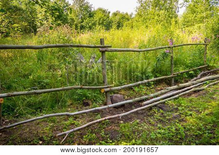 The fence is handmade from trunk of trees. The rural design of the fence site. Fence for the cattle in the village.