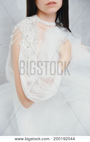 Delicate aerial photo of a bride in a white wedding dress with an airy tuxedo, close-up. Concept wedding, fashion dresses for the engagement.