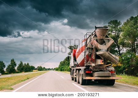 Special Concrete Transport Truck In-transit Mixer Unit In Motion On Country Road, Freeway In Europe. Asphalt Freeway, Motorway, Highway. Business Transportation And Development Concept