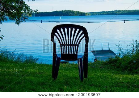 One vacant place available, empty chair by a lake