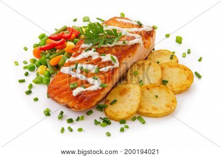Fillet of red fish salmon with fried potatoes and vegetables isolated on white background.