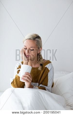 Portrait of pensive young Caucasian woman wearing sweater sitting on bed under blanket and holding tea cup