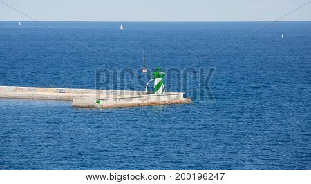 Green and White Lighthouse at end of Barcelona Seawall