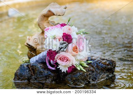 Close Up Of Beautiful Fresh Wedding Bouquet Of Pink And White Roses On Stone In Water  Near Fish In