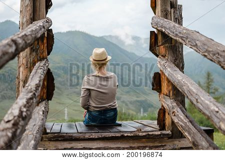 Photo Of A Woman From The Back Which Looks Out Onto The Mountains.
