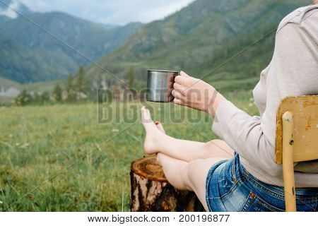 Woman Drinking A Beverage From A Metal Mug.