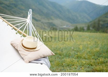 Hammock plaid and hat on the background of mountains.