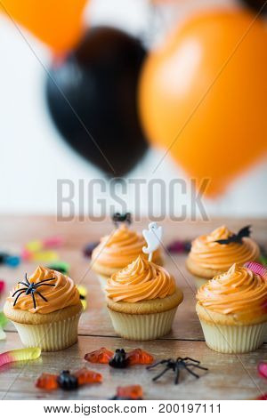 food, baking and holidays concept - cupcakes or muffins and candies with halloween party decorations on wooden table