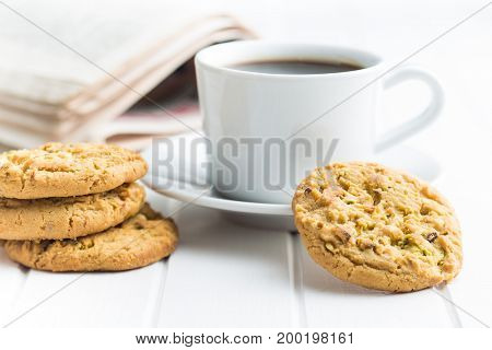 Sweet pistachio cookies and coffee mug on white table.