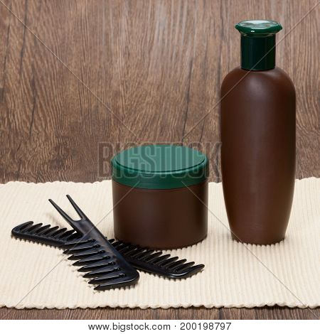 Hair care cosmetics. Shampoo and hair mask with combs. Copy space