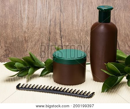 Shampoo, hair mask and comb with fresh green leaves. Natural hair care cosmetics with copy space