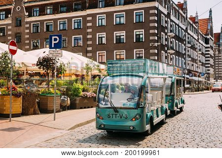 Riga, Latvia - July 2, 2016: Electric Car With Tourists People For Exploring City's Attractions Near Open Air Leisure Venue Recreation Center Egle In Sunny Day In Old Town On Kalku Street
