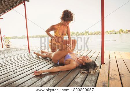 couple of women on wooden raft  exercise yoga one assists another in  stretching the leg muscles summer day