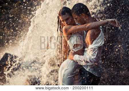 Young enamored wet couple hugs under spray and drops of waterfall. Around them are visible jets and streams of running water.