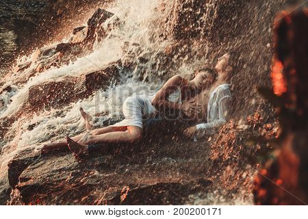 Young enamored wet couple lies on rock and hugs under spray and drops of waterfall. Around them are visible jets and streams of running water.