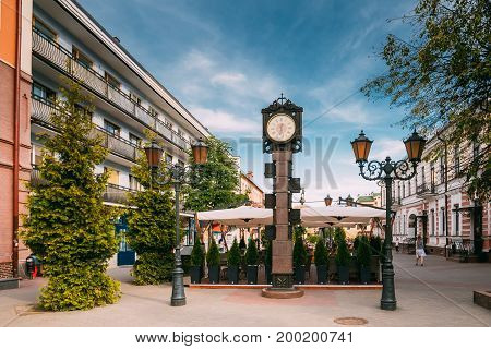 Brest, Belarus. Two-Sided Clock In Old-Fashioned Decoration With Arms Of City Of Different Times In Form Of A Six-Meter Bronze Monument On Pedestrian Sovietskaya Street In Summer Day.