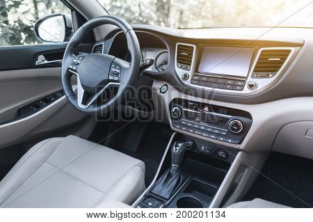 Luxury car interior - steering wheel shift lever and dashboard.