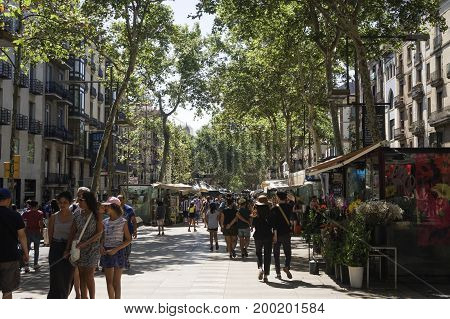 Barcelona, Spain - July 23 2017: Crowd walking on La Rambla tree lined area. The tourist popular crowded pedestrian zone of Las Ramblas.
