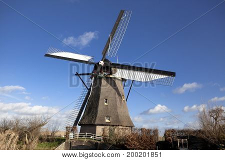 The old Dutch windmills, Holland, rural expanses . Windmills, the symbol of Holland. Holland windmill on a canal. Old mill chalk and flour