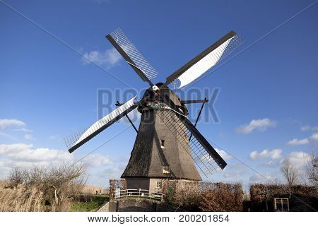 The old Dutch windmills, Holland, rural expanses . Windmills, the symbol of Holland. Holland windmill on a canal.