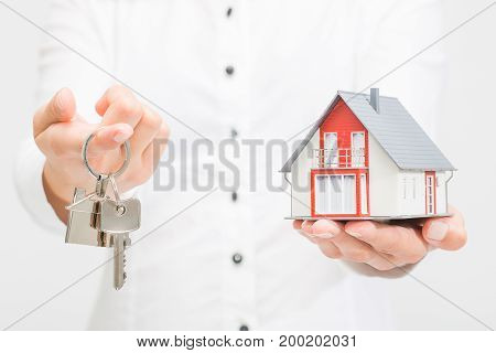 Woman holding small house and metal key.