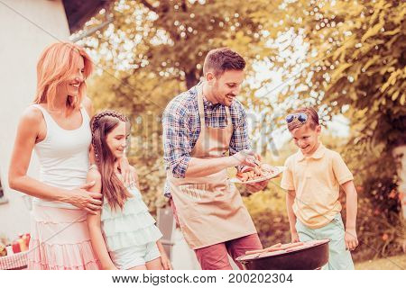 Barbecue time.Young family make barbecue at their home.
