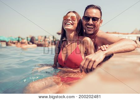 Portrait of a happy young couple relaxing on the edge of swimming pool.