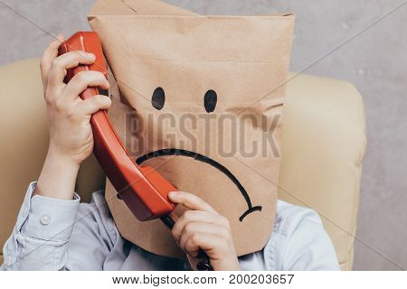 Child With Paper Bag On Head With Telephone