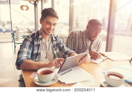 In a good mood. Positive handsome student using tablet and sitting at the table with his friends who is studying