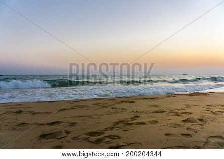 View on some Foot Prints in front of a beautiful Beach in the Morning Light. Close-uo of a Beach and Waves. Natural Background.