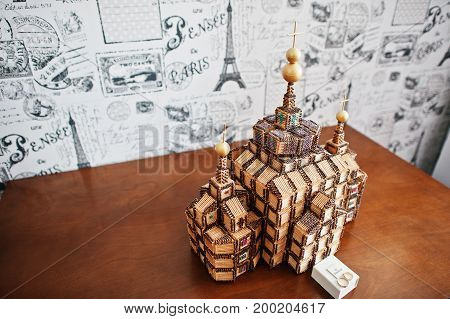 Photo Of A Small Replica Of A Wooden Church On The Table.