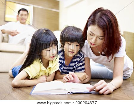 asian mother and two children lying on floor reading book while father watching in the background.