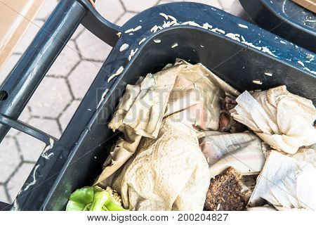 Countless crawling maggots in and around a brown organic waste bin