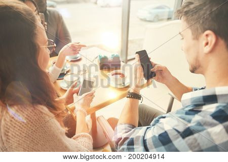 Modern igen. Positive international students using smart phones and sitting in the cafe while enjoying rest together